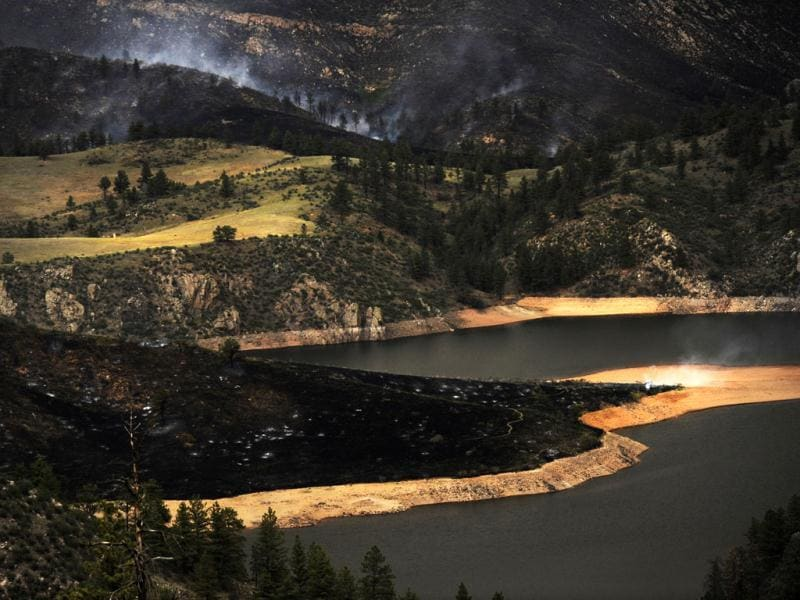 The Hewlett Gulch fire burns to the edge of Seaman Reservoir in the Poudre Canyon near Fort Collins. AP Photo/The Denver Post, RJ Sangosti