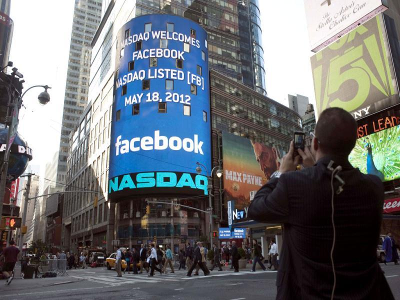 A man takes a picture of a monitor shows a welcoming message for Facebook's listing on the Nasdaq Marketsite prior to the opening bell in New York. Reuters/Keith Bedford