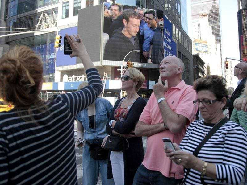 Times Square visitors react as Facebook CEO Mark Zuckerberg is shown on giant monitors, as the company's stock is set to begin trading on the Nasdaq stock market in New York. AP/Bebeto Matthews