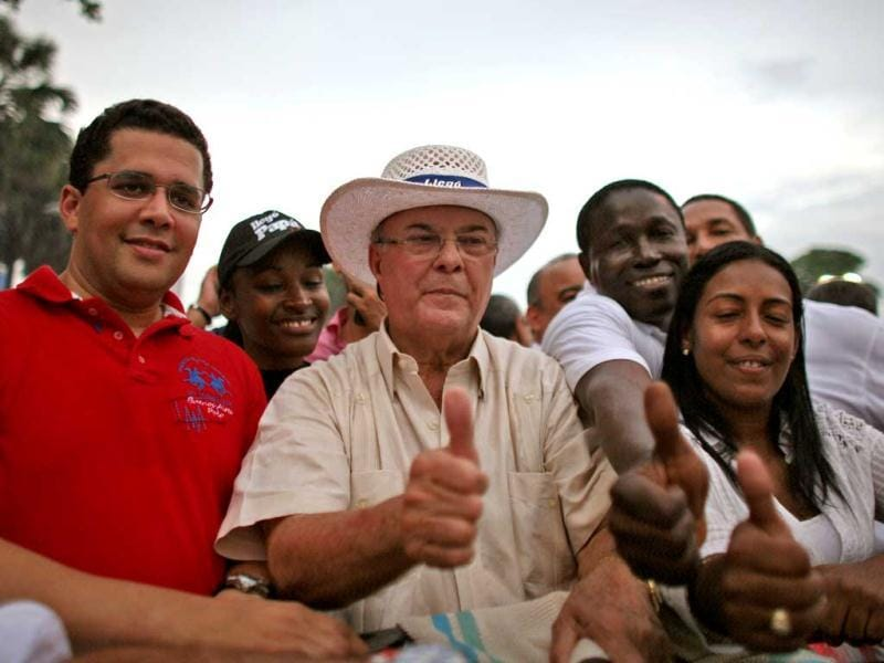 Former president and candidate for the opposition Dominican Revolutionary Party Hipolito Mejia (C) accompanied by aides, gives a thumbs up to supporters while arriving to his closing campaign rally in Santo Domingo, Dominican Republic. AP Photo/Ricardo Arduengo