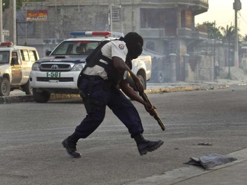 A national police officer runs toward a former army base to take a position during clashes between police and members of the dissolved army in Port-au-Prince, Haiti. AP Photo/Ramon Espinosa