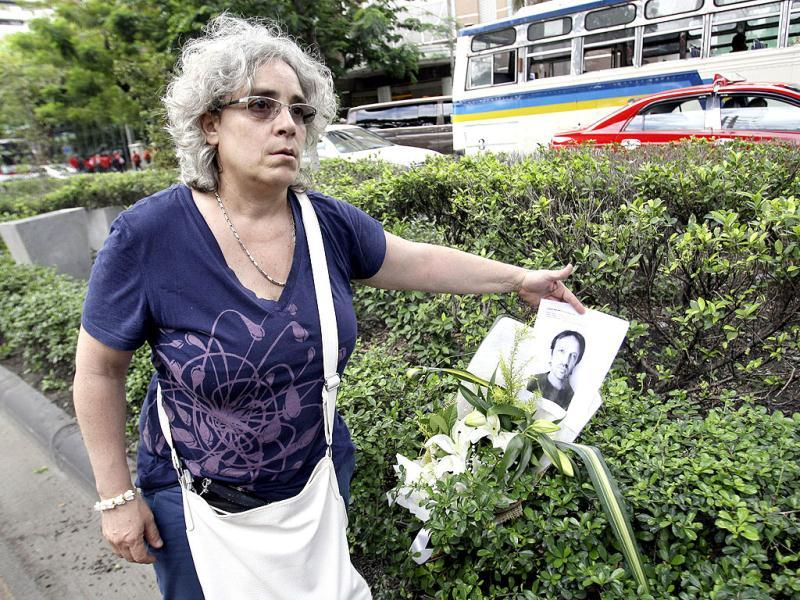 Isabella Polenghi, younger sister of Italian photographer Fabio Polenghi who was killed as troops forcibly suppressed an anti-government protest in Bangkok in 2010, places a flower and the copy of his portrait near the site where her brother was killed to commemorate the second anniversary in Bangkok. AP Photo/Sakchai Lalit