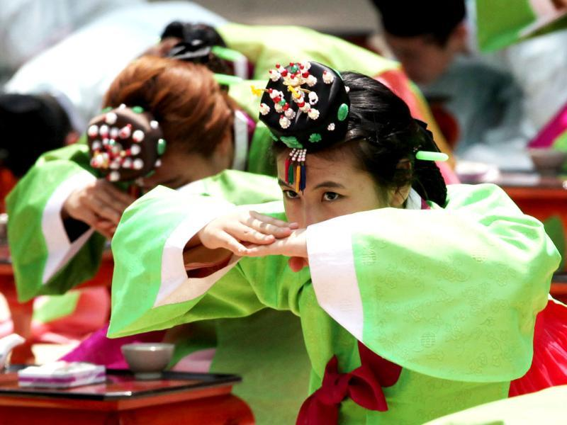 A South Korean girl in a traditional dress bows during the 40th Coming of Age Day Ceremony and re-presentation of traditional