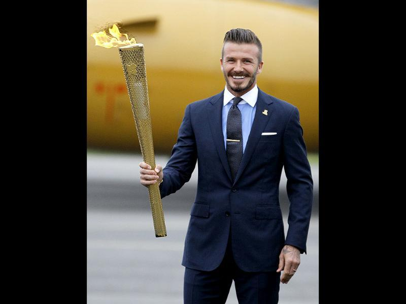 Britain's David Beckham holds the Olympic torch during the ceremony to mark the arrival of the Olympic flame to Britain from Greece, at RNAS Culdrose, Cornwall, England. AP/Alastair Grant