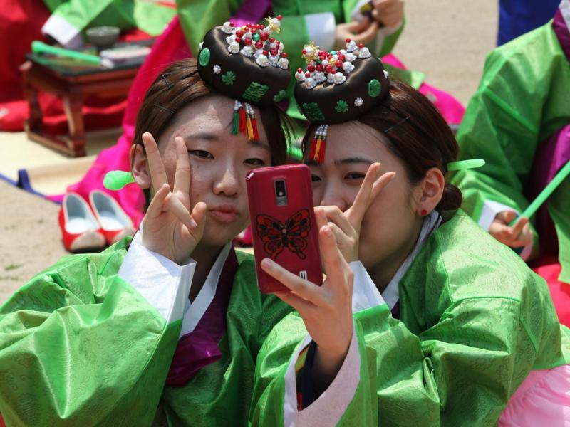South Korean girls in traditional dresses take a picture of themselves after the 40th Coming of Age Day Ceremony and re-presentation of traditional