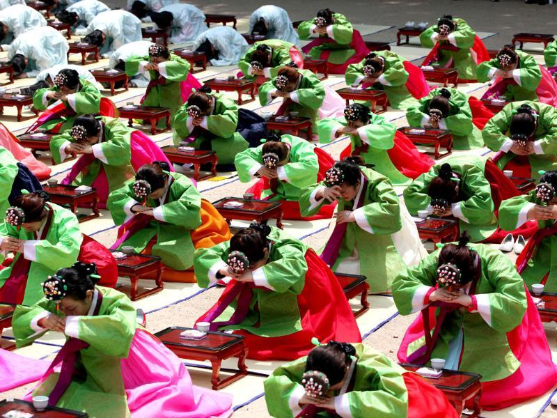 South Korean girls and boys in traditional dresses bow during the 40th Coming of Age Day Ceremony and re-presentation of traditional
