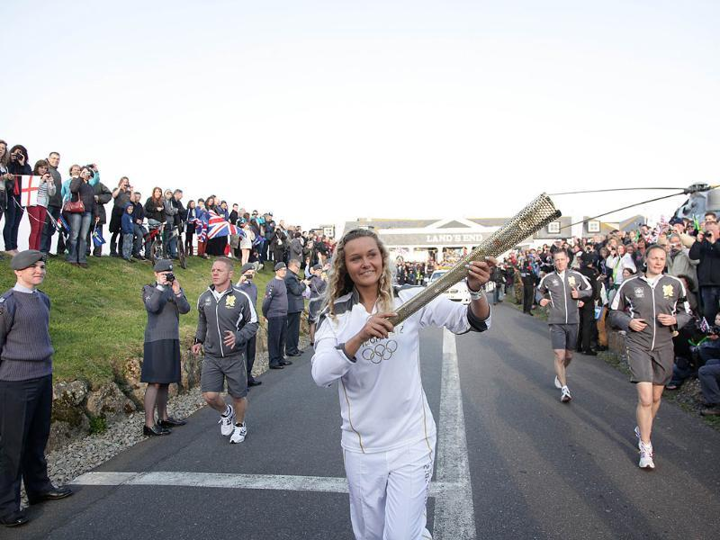 Anastassia Swallow (C), the second torchbearer runs holding the Olympic flame at Land's End, the southwesterly tip of England at the start of the torch relay around Britain and Ireland. AFP photo