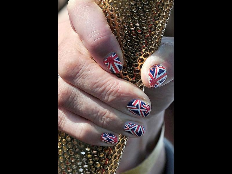 Olympic Torch bearer, Sarah Blight, with Union Flag-painted finger nails holds the torch on the beach near St Michael's Mount in Cornwall, south-west England. AFP/Carl Court