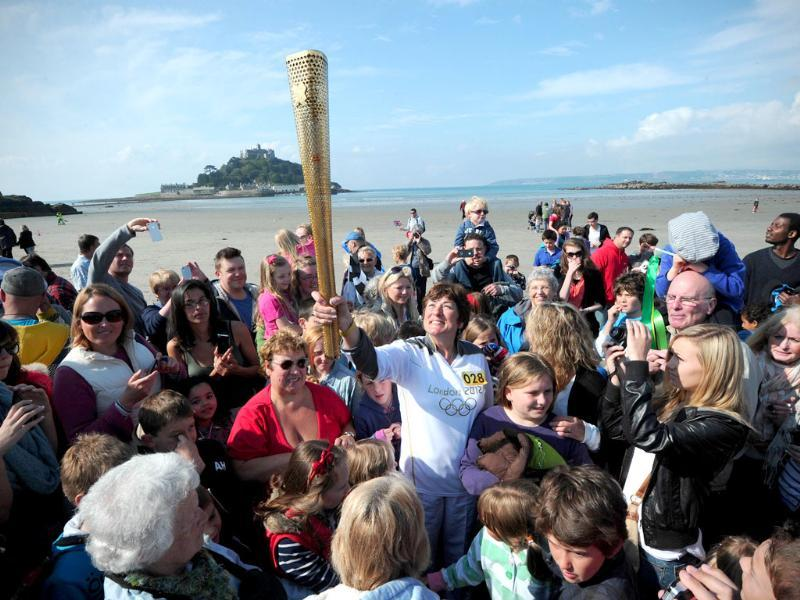 Members of the public crowd around Olympic Torch bearer, Sarah Blight, as she holds the torch on the beach near St Michael's Mount in Cornwall, south-west England. AFP/Carl Court