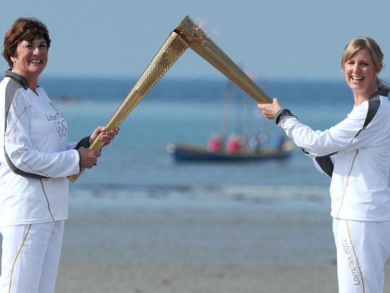 Olympic Torch bearers exchange the flame on the beach near St Michael's Mount in Cornwall, south-west England. AFP/Carl Court