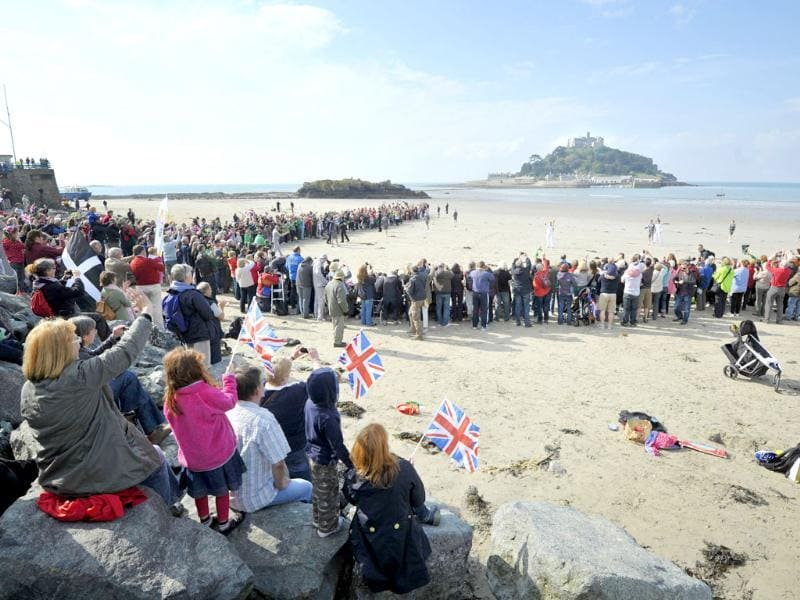 Crowds watch as torchbearer Johanna Dickinson waves as she holds the torch on the beach at Marazion, looking out to St Michael's Mount, during the leg of the torch relay between Newlyn and Marazion south west England. AP Photo/Tim Ireland