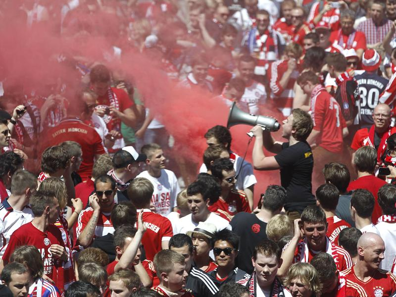 A steward uses a megaphone to control Bayern Munich supporters on the streets of Munich, Germany. (AP Photo/Matthias Schrader)