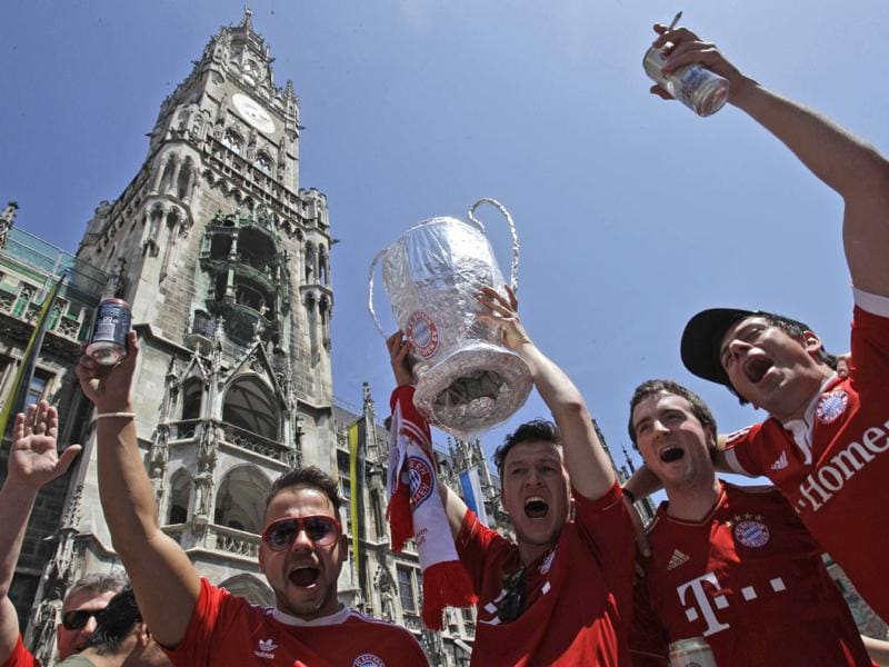 Bayern Munich supporters hold up a homemade replica of the Champions League trophy as they gather on the streets of Munich, Germany.  (AP Photo/Frank Augstein)