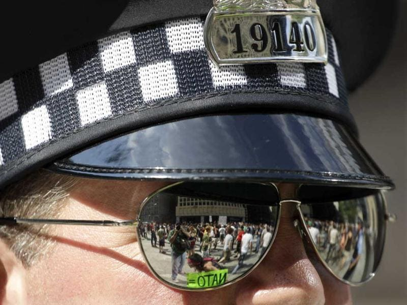 Nato protesters are reflected in a Chicago police officers sunglasses during a march in Daley Plaza, in Chicago. Security has been high throughout the city in preparation for the NATO summit, where delegations from about 60 countries will discuss the war in Afghanistan and European missile defense. AP Photo/M Spencer Green