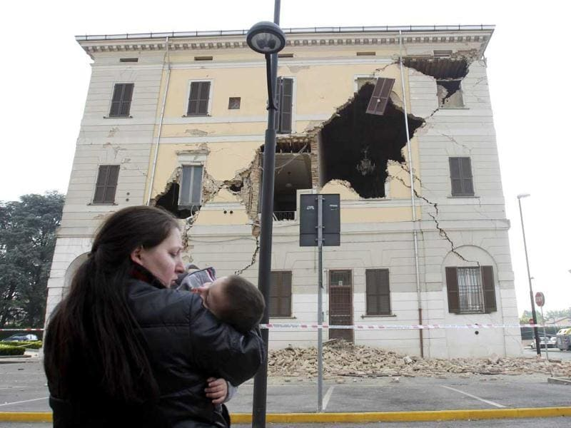 A woman carrying her child stands on the street in front of the Town Hall building, damaged by an earthquake, on Sant' Agostino, near Ferrara. A strong earthquake rocked a large swathe of northern Italy. Reuters/Giorgio Benvenuti