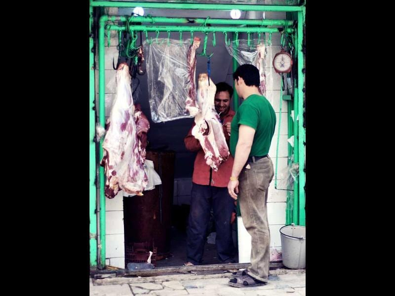 An Afghan meat vendor serves a customer at his shop in Kabul. Poverty and an ongoing insurgency by the ousted Taliban still pose a threat to the stability of the country. AFP/Bay Ismoyo