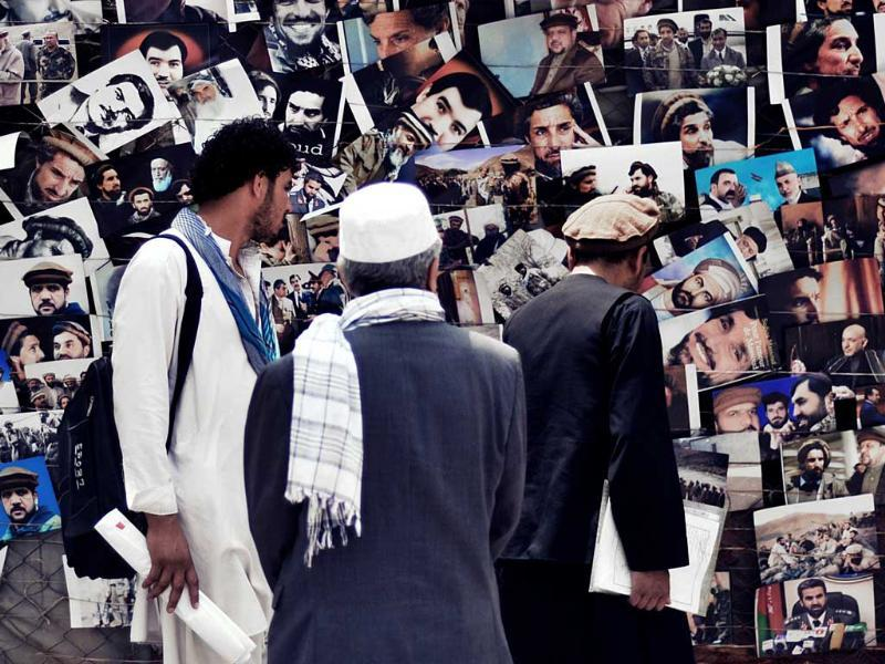 Afghan men browse for pictures of their heroes and leaders at a sidewalk stall in Kabul. AFP/Bay Ismoyo
