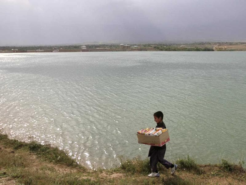 A boy sells biscuits as he walks along a lake in Kabul. Reuters/Mohammad Ismail