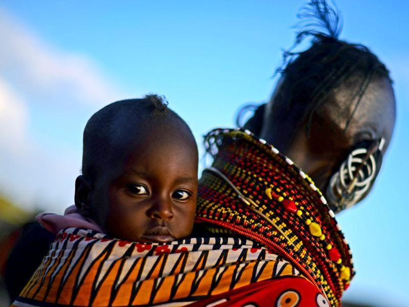 A woman from the Turkana tribe carries a baby on her back at the Lake Turkana Festival in Loiyangalani, near Lake Turkarna in Northern Kenya. The festival is an annual cultural festival designed to promote tourism in the area and to forge better relationships between the seven different tribes in the area. AFP/Carl De Souza