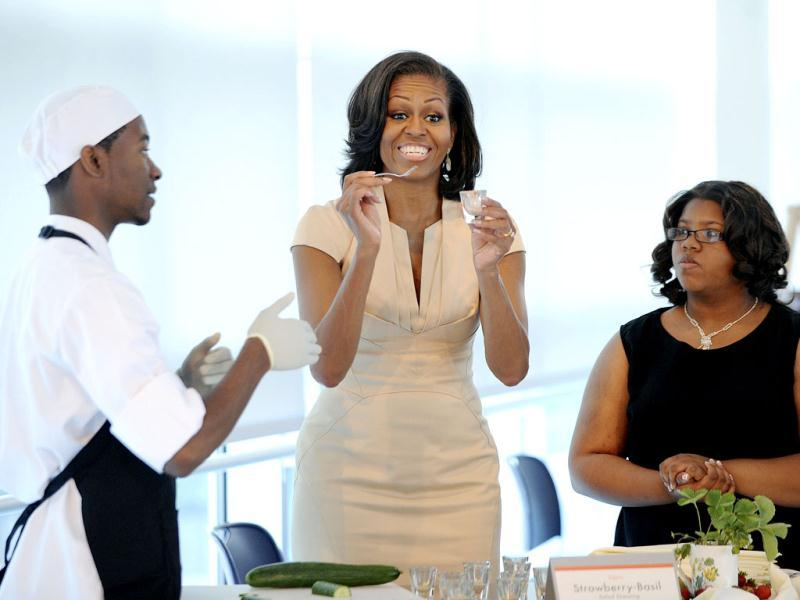 US First Lady Michelle Obama reacts as she tastes food that students make for the lunch with the Nato leaders Spouses at the Gary Corner Youth Center in Chicago. AP/Olivier Douliery, Pool
