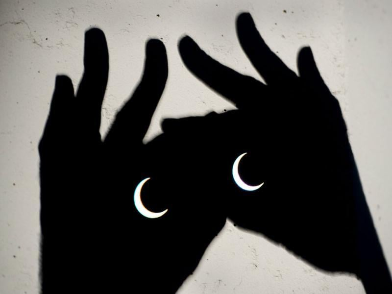 The annular eclipse is visible through binoculars in Sacramento, Calif. The annular eclipse, in which the moon passes in front of the sun leaving only a golden ring around its edges, was visible to wide areas across China, Japan and elsewhere in the region before moving across the Pacific to be seen in parts of the western United States. AP Photo/The Sacramento Bee, Randy Pench