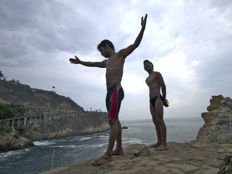 Cliff divers prepare to jump at La Quebrada in Acapulco, Mexico. The tradition of 'La Quebrada' goes back to 1934, when two neighbors of Acapulco challenged themselves to show their courage and decided to measure their forces by throwing themselves into the sea from the top of a cliff. The rivalry between those two men ended first in a reckless spectacle, and later in a way of earning a living. The myth of 'La Quebrada' was born, and today it is almost a religion for its followers. AFP PHOTO/PEDRO PARDO