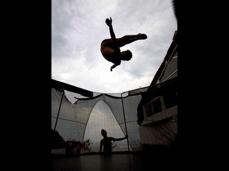 Bryant Ramirez, a 14 year-old cliff diver, practices in an elastic trampoline before jumping at La Quebrada in Acapulco, Mexico. The tradition of 'La Quebrada' goes back to 1934, when two neighbors of Acapulco challenged themselves to show their courage and decided to measure their forces by throwing themselves into the sea from the top of a cliff. AFP PHOTO/PEDRO PARDO