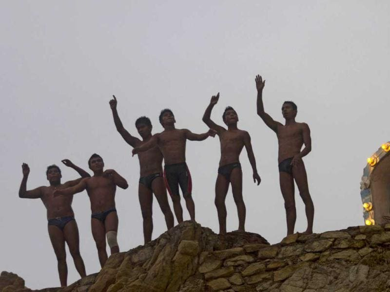 Cliff divers wave before jumping at La Quebrada in Acapulco, Mexico. The tradition of 'La Quebrada' goes back to 1934, when two neighbors of Acapulco challenged themselves to show their courage and decided to measure their forces by throwing themselves into the sea from the top of a cliff. The rivalry between those two men ended first in a reckless spectacle, and later in a way of earning a living. The myth of 'La Quebrada' was born, and today it is almost a religion for its followers. AFP PHOTO/PEDRO PARDO