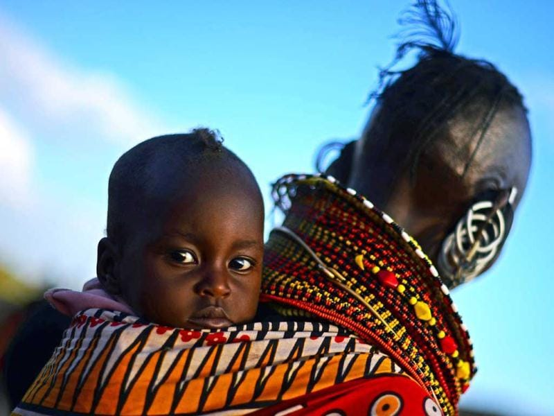 A woman from the Turkana tribe carries a baby on her back at the Lake Turkana Festival in Loiyangalani, near Lake Turkarna in Northern Kenya. The festival is an annual cultural festival designed to promote tourism in the area and to forge better relationships between the seven different tribes in the area. (AFP Photo)