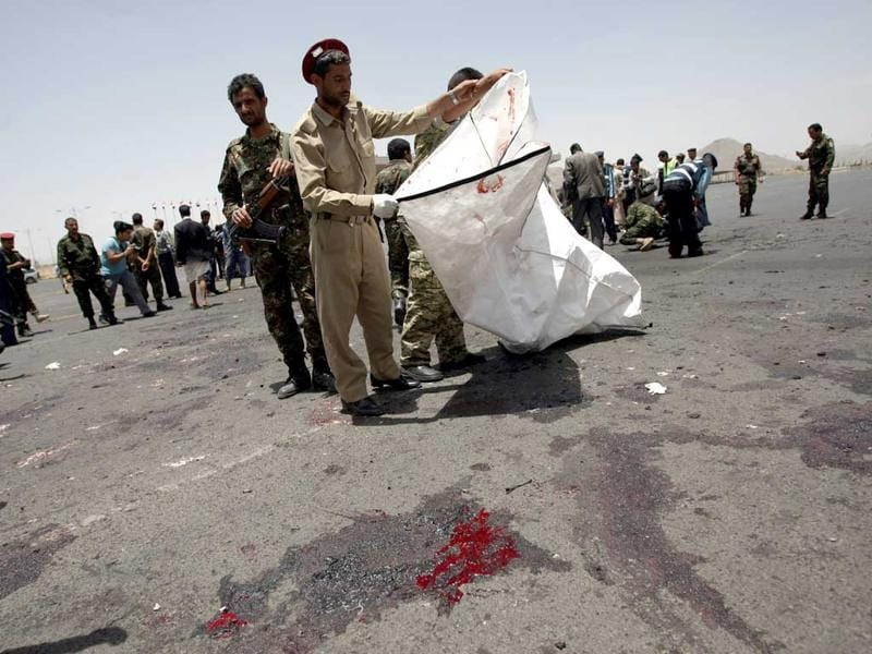 Forensic policemen collect evidence at the site of a suicide bomb attack in Sanaa. AFP/ Mohammed Huwais