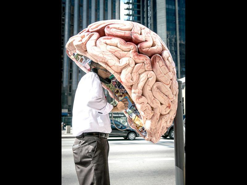 A man uses a public phone booth decorated as a brain in Sao Paulo, Brazil. A hundred phone booths, nicknamed Orelhao (meaning
