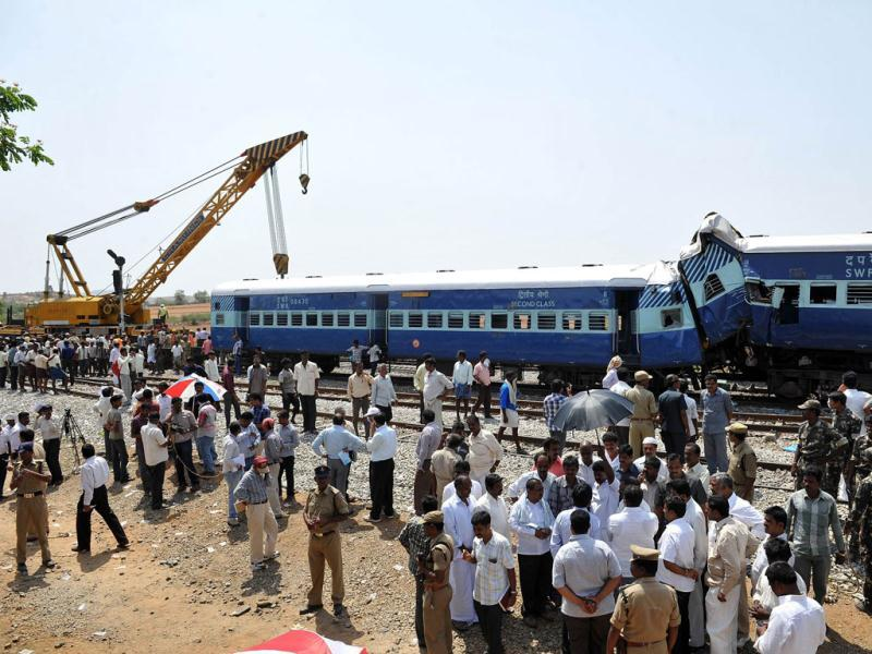 Railway officials and onlookers watch the clear up operation of the mangled remains of the Bangalore-bound Hampi Express after it collided with a stationary goods train in Ananthpur district, about 145km from Bangalore. AFP/Manjunath Kiran
