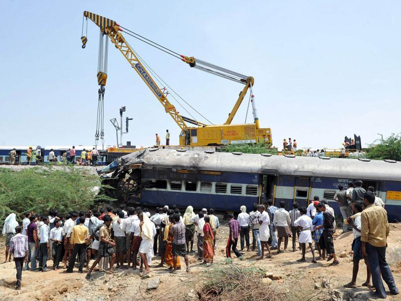 Local villagers watch as a heavy duty railway crane lifts the mangled remains of a coach of the Bangalore-bound Hampi Express. AFP/Manjunath Kiran