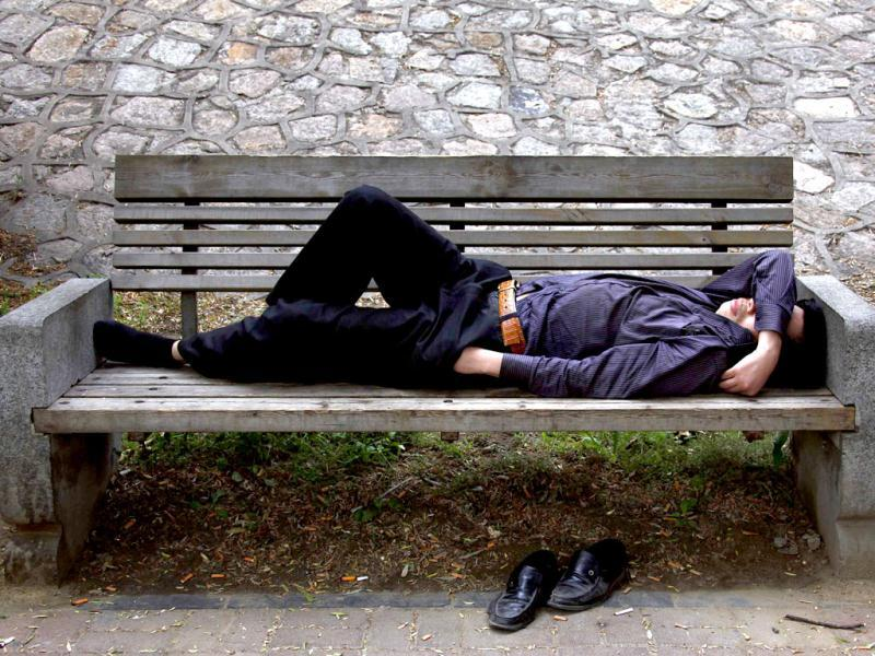 A man sleeps on a park bench with his hand in his pocket in Beijing. Reuters Photo/David Gray