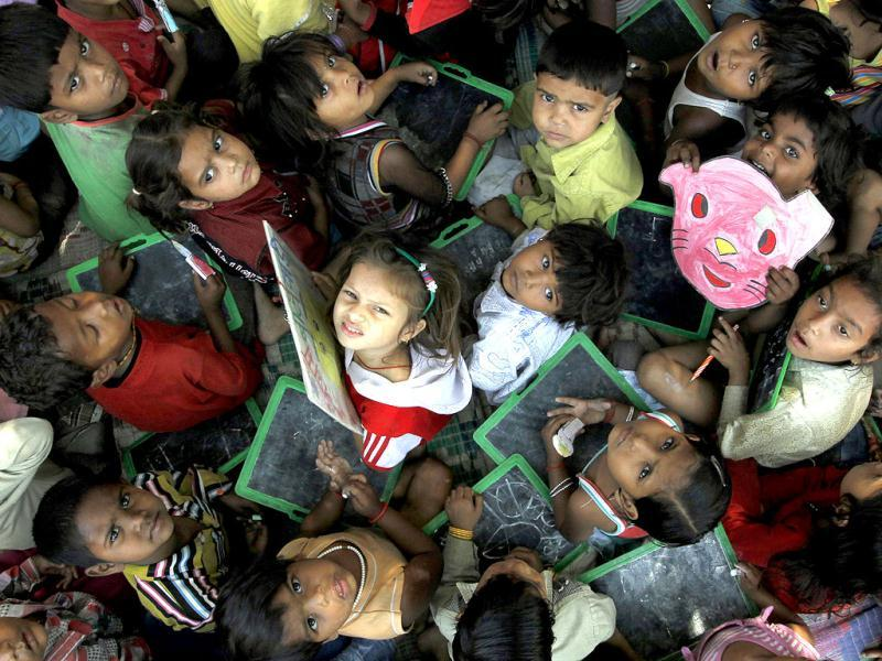 Crammed in a room, children learn to read and write at a creche in New Delhi's Daya Basti. HT/Raj K Raj
