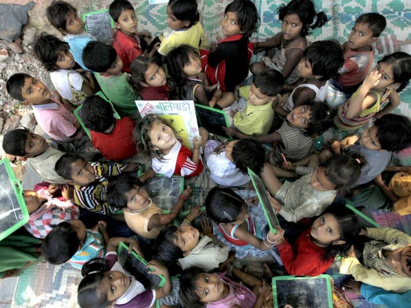 A small girl smiles at the camera at a creche in Daya Basti, New Delhi. HT/Raj K Raj