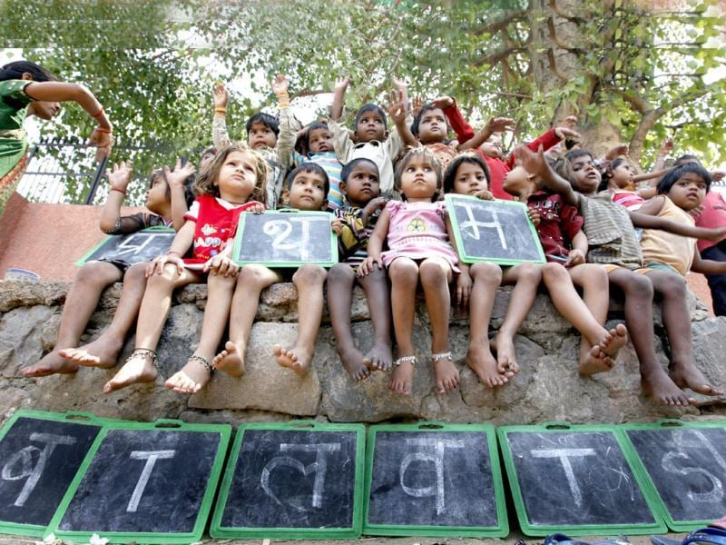 Children listen to a teacher at a creche in Daya Basti in New Delhi. HT/Raj K Raj