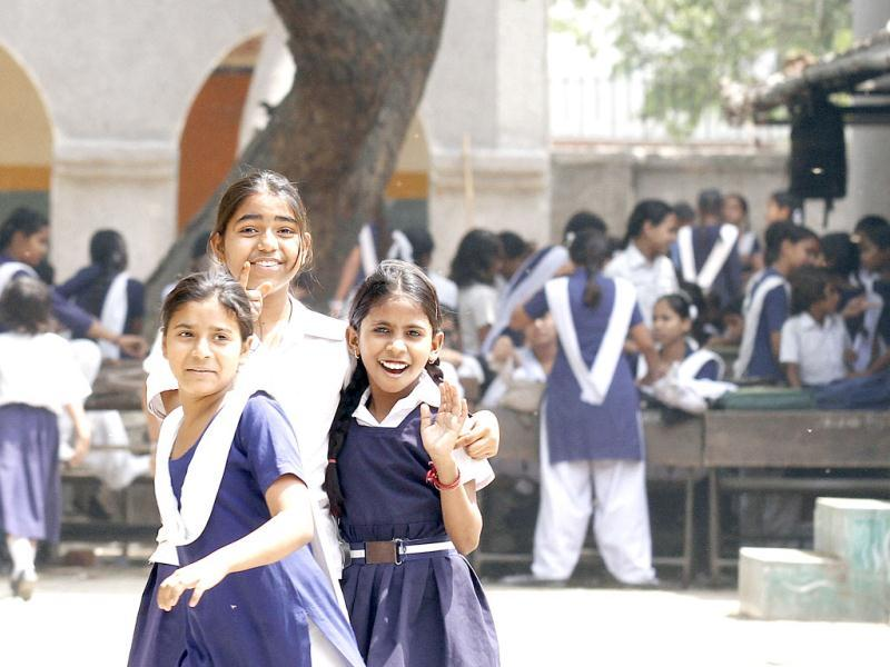 Students smile at the camera outside their class held in the open due to lack of space in Sarvodaya Kanya Vidyalaya in New Seema Puri. HT/Jasjeet Plaha