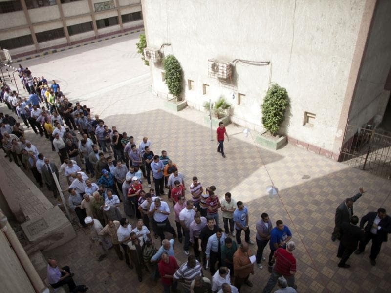 Egyptian men line up to vote outside a polling station in Cairo, as polls opened in the country's historic presidential election, the first since a popular uprising toppled Hosni Mubarak. AFP/Marco Longari