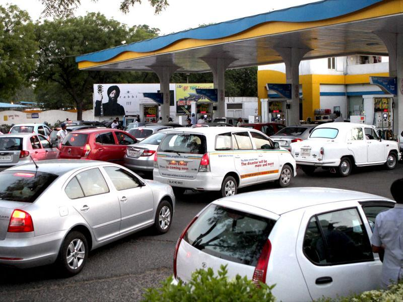 People line up to fill their vehicles at an oil pump in New Delhi after the announcement of hike in petrol prices. PTI/Kamal Singh
