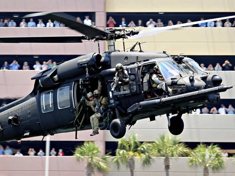 Spectators watch a demonstration by special operations troops on an Army MH-60 Blackhawk near the Tampa Convention Center during the Special Operations Forces (SOF) Industry Conference involving SOF delegates from 96 nations in Tampa. AP Photo
