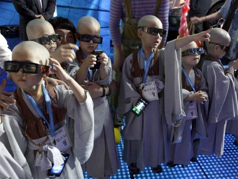 Shaven-headed young boys wearing 3-D glasses watch a movie at SK Telecom T.um Museum in Seoul, South Korea. AP Photo/Lee Jin-man