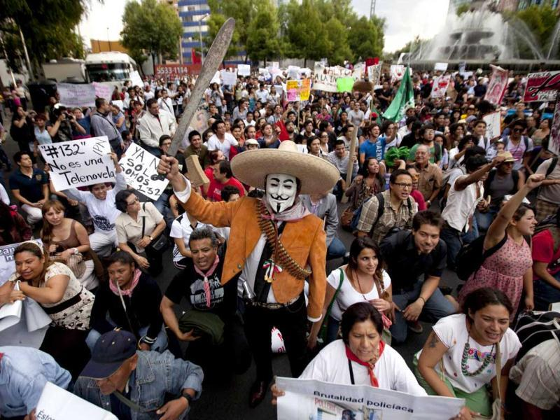 A man wearing a mask holds up a machete during a protest against a possible return of the old ruling Institutional Revolutionary Party (PRI) in Mexico City. AP Photo/Eduardo Verdugo