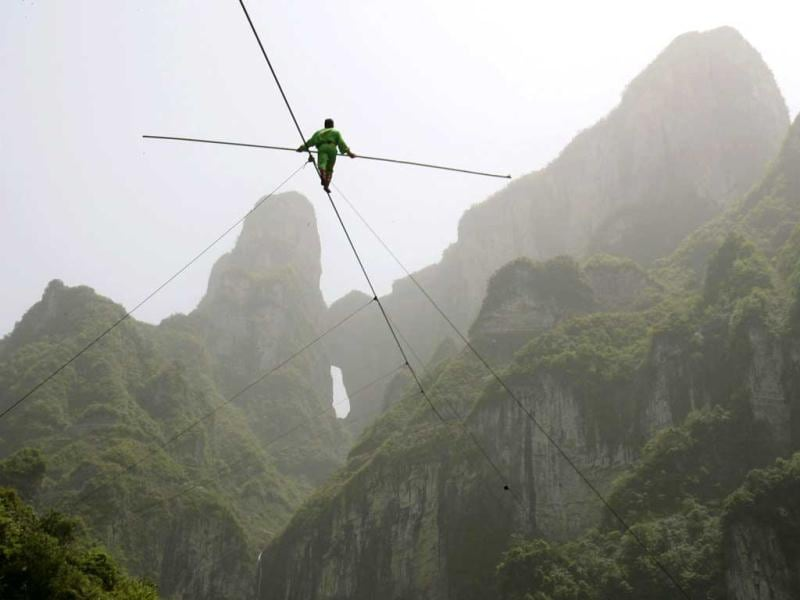 Samat Hasan, a stuntman from Xinjiang Uighur Autonomous Region, walks on a tightrope in Zhangjiajie, Hunan province. Walking on a 700-metre-long (2,300 ft) rope with a 3.1-centimetre (1.2 inches) diameter and set at a 39-degree gradient, Hasan successfully broke the Guinness Word Record for aerial tightrope walking. Reuters/China Daily, Files