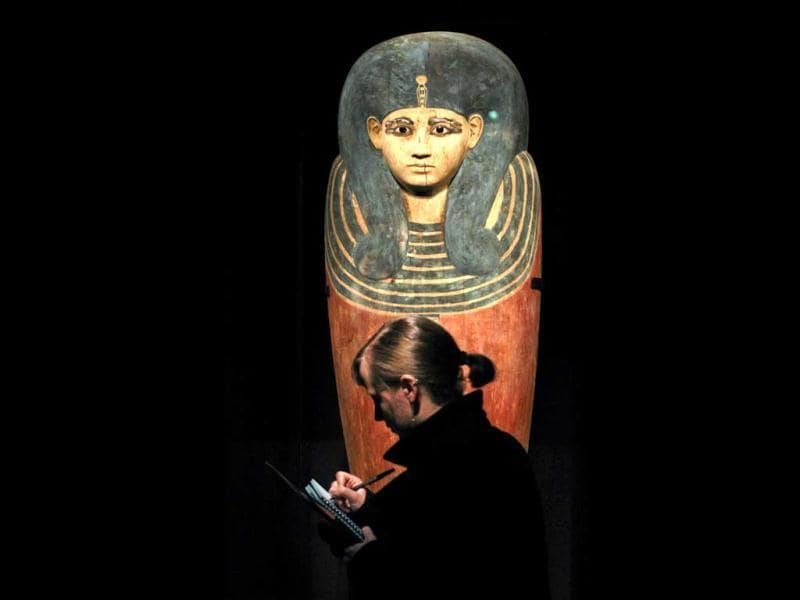 A visitor takes notes while standing in front of the inner coffin of Queen Meritamun during a preview of a King Tut exhibit in Seattle. AP/Elaine Thompson