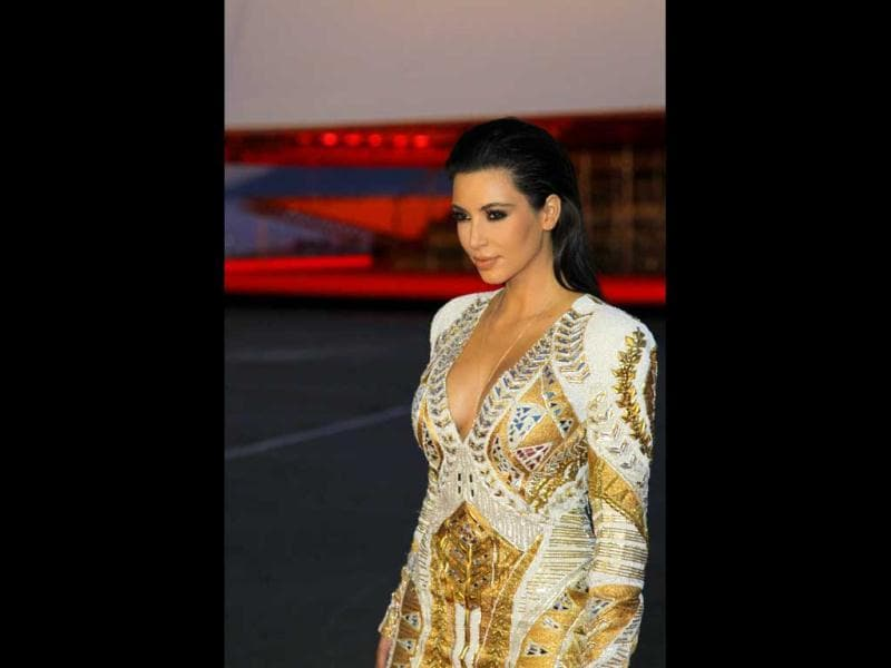 Kim Kardashian was seen sporting a short gold and cream dress, teamed with black boots.