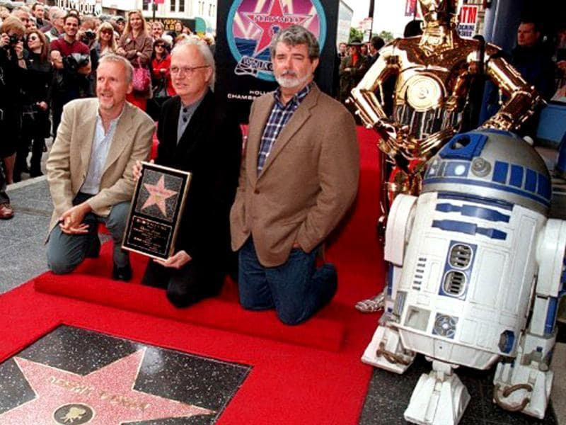 Academy Award winning special effects creator Dennis Muren (holding star) poses for photos with director James Cameron (L) and Star Wars creator George Lucas (R), who kneels next to Star Wars characters R2D2 and C3PO during a ceremony honoring Muren with a star on the famous Hollywood Walk of Fame on 3 June 1999 in Hollywood, CA.