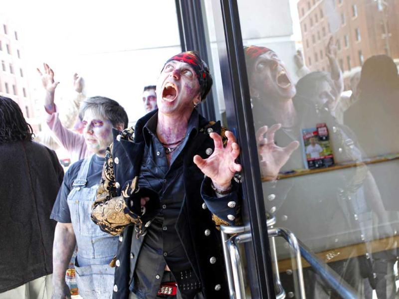 A zombie visits an entrance of a game company office as a group of zombies march around streets of San Francisco to promote Zynga's new zombie game for iPhone on May 24, 2012 in California. AFP PHOTO / Kimihiro Hoshino
