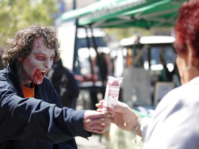 A zombie gives a free blood pop to a woman as a group of zombies march around streets of San Francisco to promote Zynga's new zombie game for iPhone on May 24, 2012 in california. AFP PHOTO / Kimihiro Hoshino