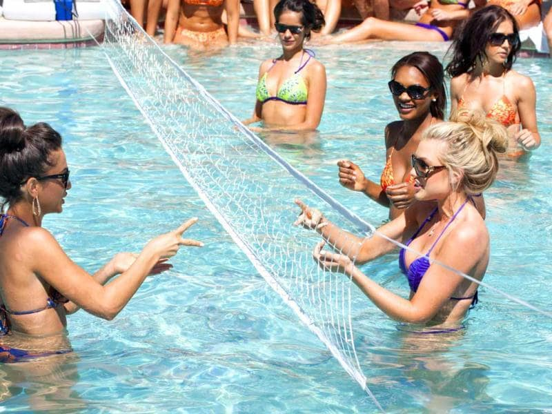 Miss Mississippi USA 2012, Myverick Rashea Garcia; and Miss Arizona USA 2012, Erika Lane Frantzve; play rock paper scissors to see what team gets the serve for the Miss USA 2012 volleyball game during the OPTX Rhode Island pool party at the Flamingo Hotel in Las Vegas, Nevada. (AFP Photo)